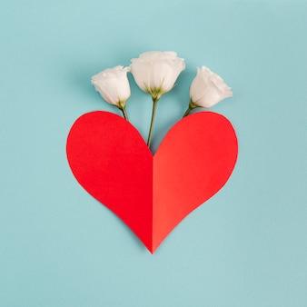 Corazón de papel rojo cerca de flores frescas