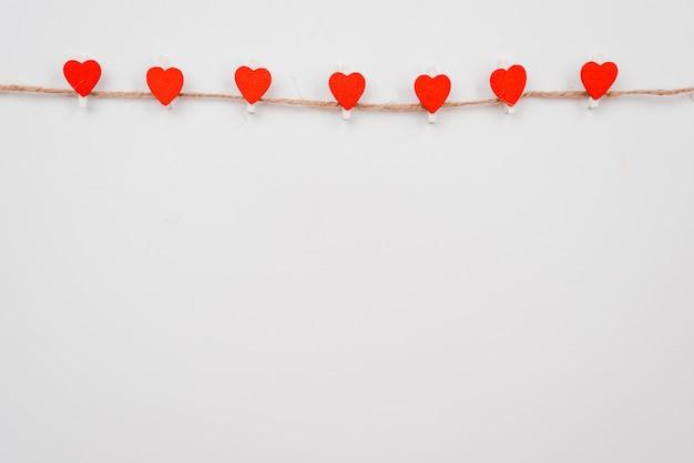 Corazón de papel rojo colgado en el tendedero en la pared blanca