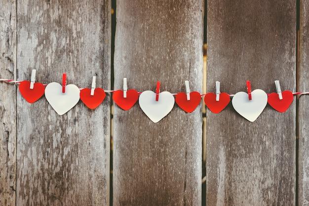 Corazón de papel rojo colgando en el tendedero