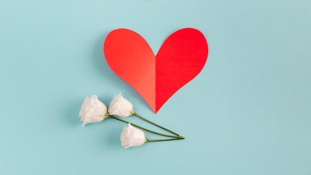 Corazón de papel rojo y flores.