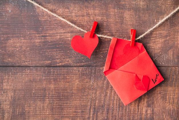 Corazón de papel rojo y sobre con alfileres enganchados con giro