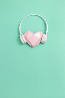 Corazón de papel rosa en auriculares blancos