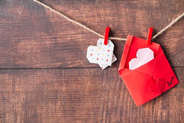 Corazón de papel y sobre con alfileres que enganchan en el giro