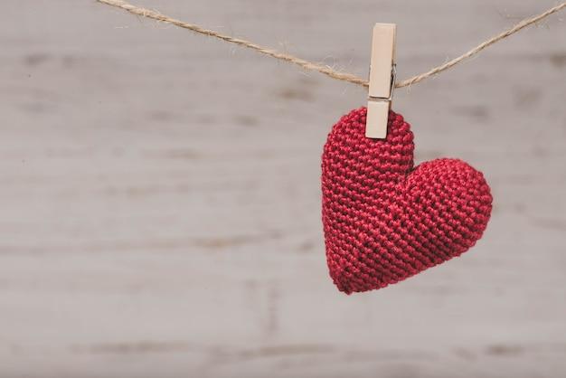 Corazón de peluche rojo colgando de una cuerda