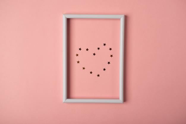 El corazón de pequeñas estrellas doradas en el marco de fotos blanco sobre fondo rosa. concepto de san valentín. vista plana endecha, superior.