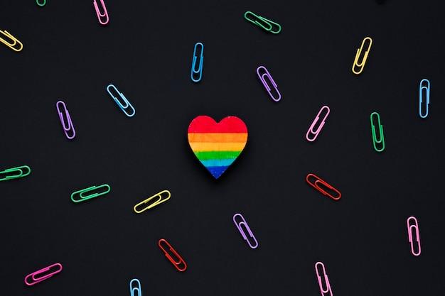 Corazón pequeño arco iris con clips en la mesa