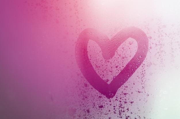 El corazón está pintado sobre el vidrio empañado en el invierno.