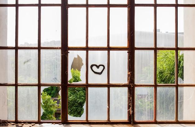 Corazón pintado en ventanas rotas.
