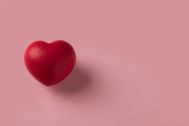 Corazón rojo aislado sobre un fondo rosa. concepto de san valentín. pasión y símbolo romántico. copie el espacio para el texto.