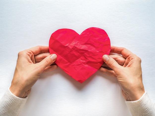 Corazón rojo arrugado de papel. el símbolo de un corazón roto.