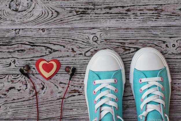 Corazón rojo y blanco con auriculares y zapatillas turquesas n piso de madera. estilo deportivo. endecha plana. la vista desde arriba.