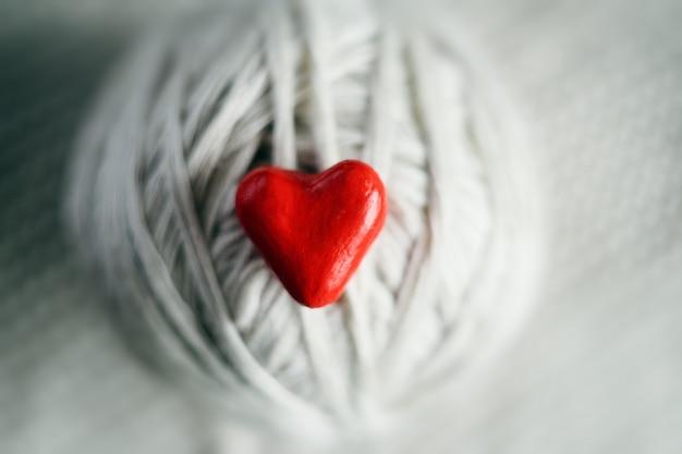 Corazón rojo y una bola de hilos en un fondo de punto