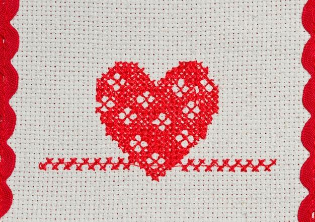 Corazón rojo bordado en punto de cruz sobre lienzo.