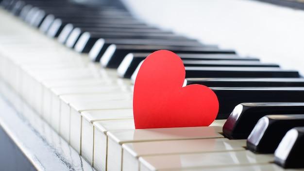 Corazón rojo brillante en un teclado de un viejo piano. concepto de amor, día de san valentín