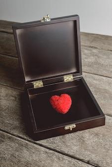 Corazón rojo en caja de joyería vintage, que se encuentra en las tablas