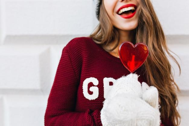 Corazón rojo caramelo sosteniendo por chica en guantes blancos. ella tiene cabello largo, sonrisa blanca como la nieve, labios rojos.