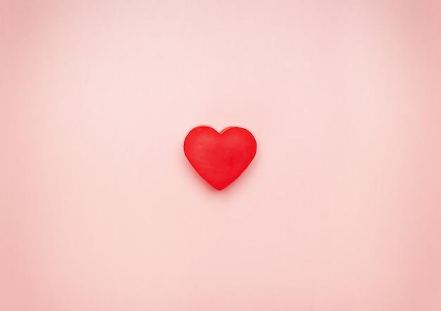 Corazón rojo en el centro de un fondo rosa