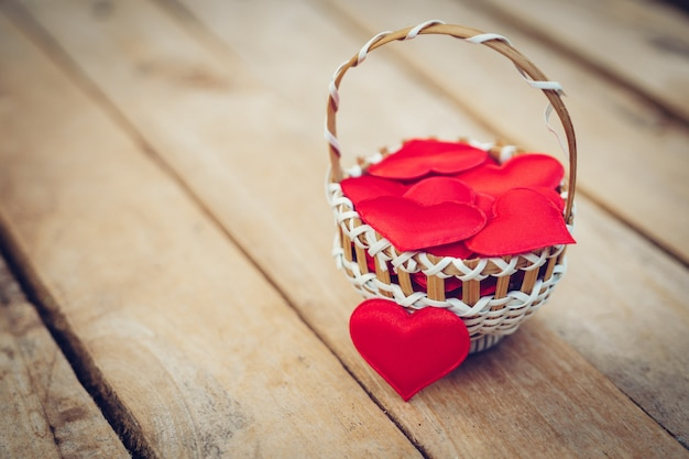 Corazón rojo en cesta en la mesa de madera para el día de san valentín y el concepto de amor