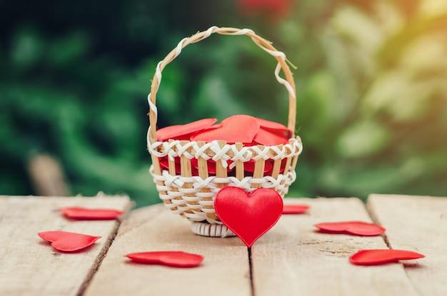 Corazón rojo en cesta en la tabla de madera para el día de san valentín y el concepto del amor con el espacio de la copia.