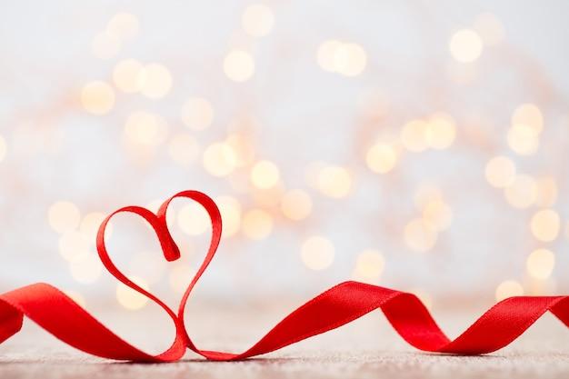 Corazón rojo cinta roja en forma de corazón fondo bokeh