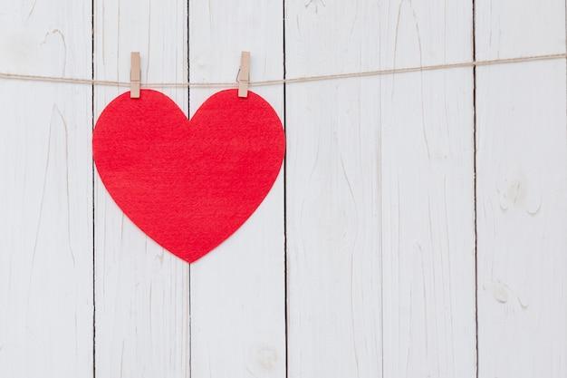 Corazón rojo colgando sobre fondo de madera blanco