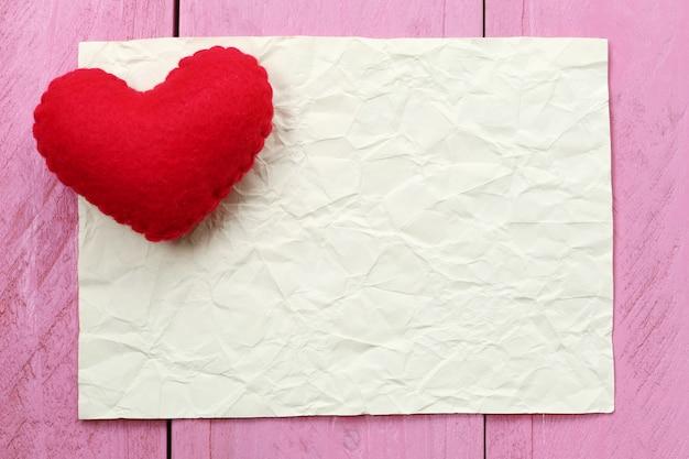 El corazón rojo colocado en la nota de papel de vacío para el texto o el mensaje de entrada en diseño.