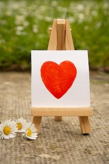 Corazón rojo, corazón de la acuarela del drenaje de la mano en la etiqueta engomada blanca. concepto de amor