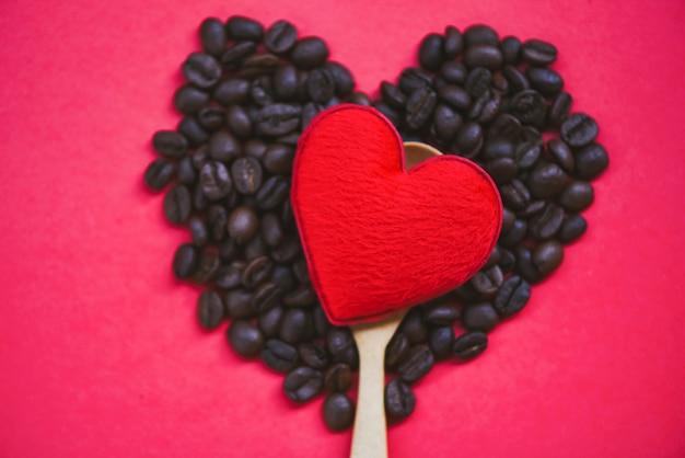 Corazón rojo en cuchara de madera y granos de café amor romántico día de san valentín en rojo