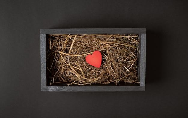 Un corazón rojo dentro de una caja de madera negra con heno (hierba seca) sobre el fondo oscuro (negro). concepto de san valentín. vista plana endecha, superior.