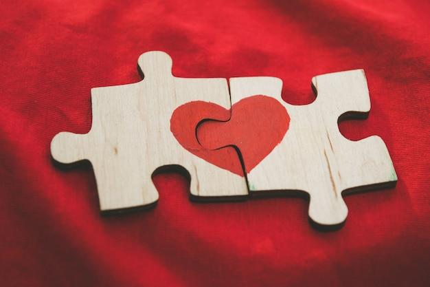 El corazón rojo se dibuja en las piezas del rompecabezas de madera que se encuentran una al lado de la otra sobre fondo rojo.