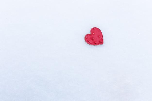 Corazón rojo se encuentra en la nieve, concepto de vacaciones de san valentín, espacio para una inscripción.