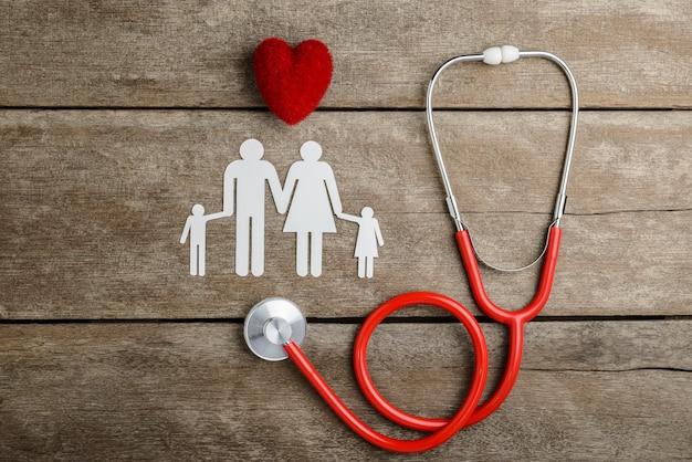 Corazón rojo, estetoscopio y familia de cadenas de papel en mesa de madera