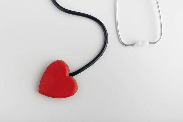 Corazón rojo y un estetoscopio, fondo blanco. sigue a tu corazón. concepto de salud.