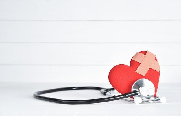Corazón rojo con el estetoscopio en el fondo de madera blanco.