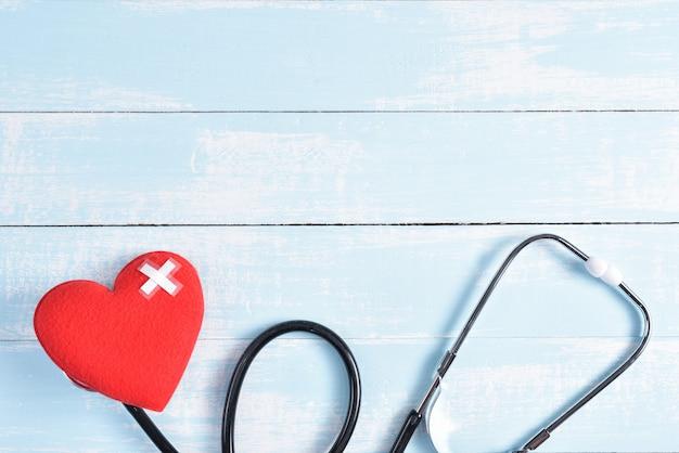Corazón rojo con el estetoscopio en fondo de madera en colores pastel azul y blanco.