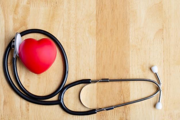Corazón rojo y estetoscopio en mesa de madera