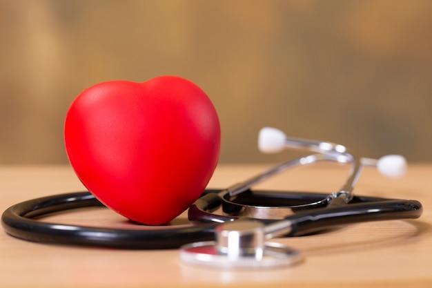 Corazón rojo y estetoscopio en mesa de madera.