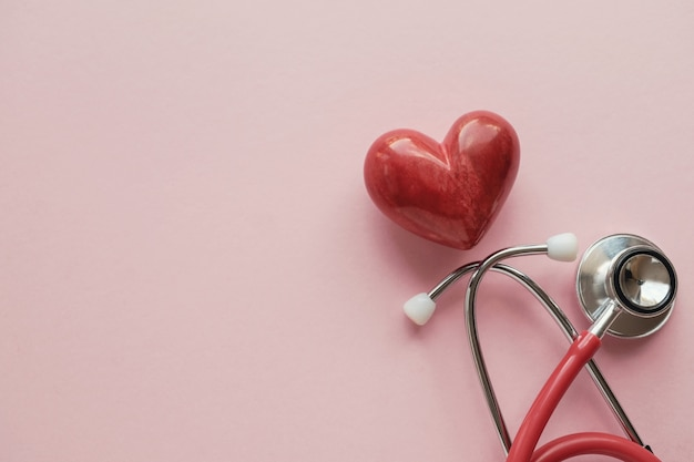 Corazón rojo con estetoscopio sobre fondo rosa