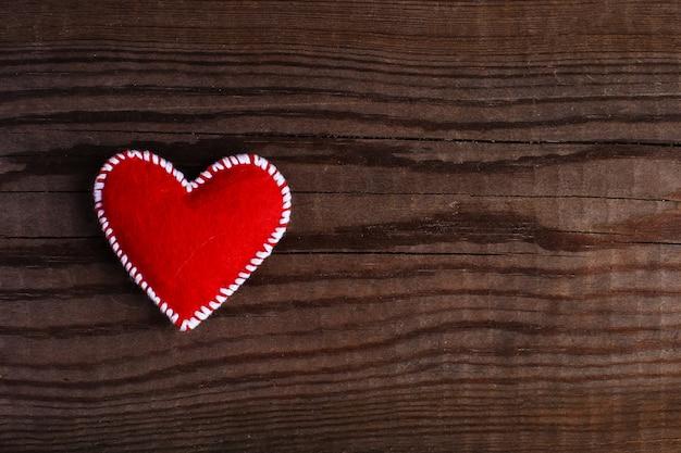 Corazón rojo de fieltro sobre una mesa de madera