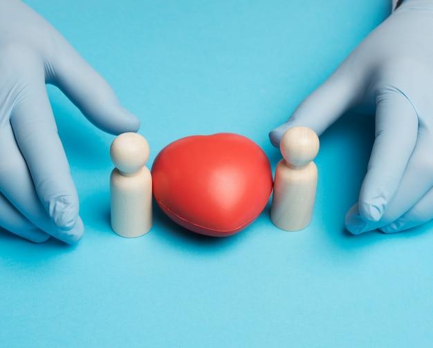 Corazón rojo y figurillas de madera de una familia, manos del médico en guantes azules, cerrar