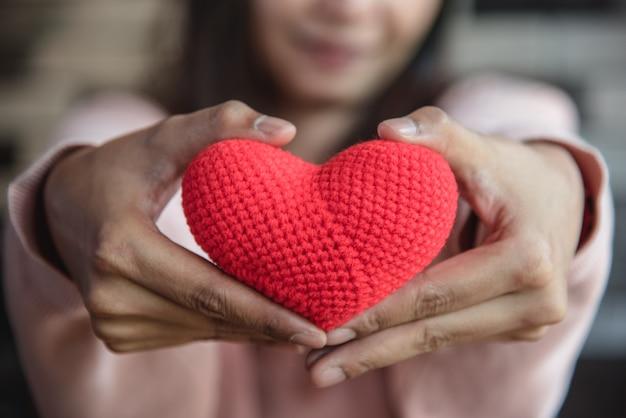 Corazón rojo grande del hilado que se sostiene y que da al frente por la mano de la mujer.