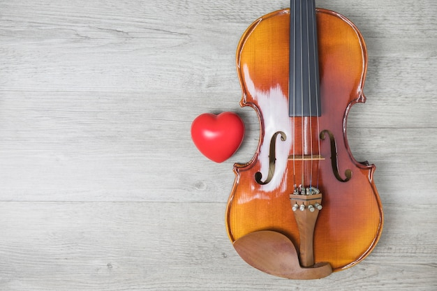 Corazón rojo y guitarra clásica de madera en la mesa gris
