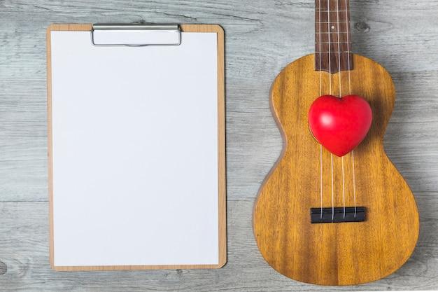 Corazón rojo; guitarra y libro blanco en portapapeles sobre el fondo de madera
