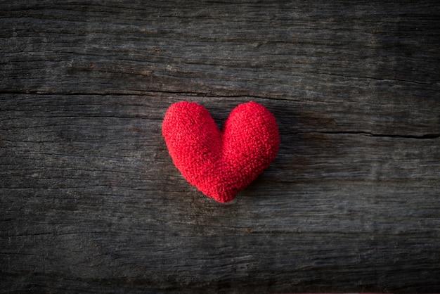 Corazón rojo hecho a mano solo en fondo de madera. corazón roto concepto.