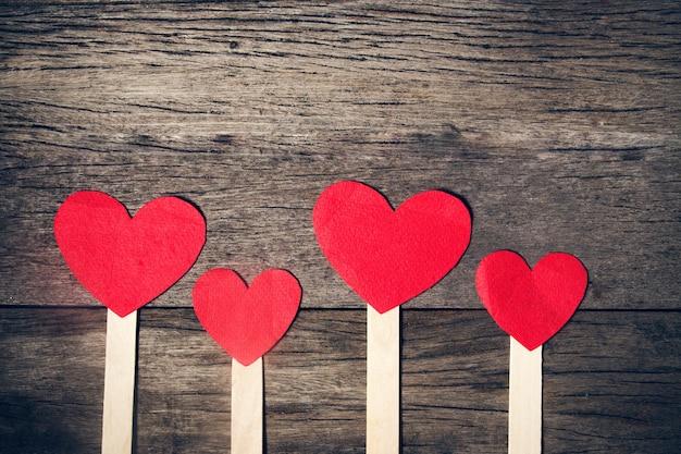 Corazón rojo hecho de papel en el fondo de madera. color de la vendimia