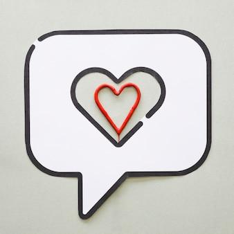 Corazón rojo en el icono de discurso de burbuja en la mesa