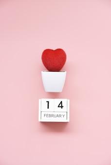 Corazón rojo en macetas blancas sobre fondo rosa para el 14 de febrero endecha plana
