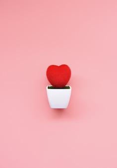 Corazón rojo en macetas blancas sobre fondo rosa
