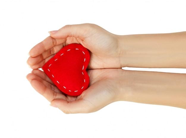 Corazón rojo en manos aisladas