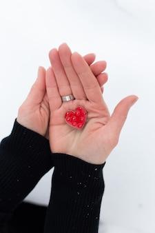 Corazón rojo en manos de una niña en una pared ligera, está nevando.